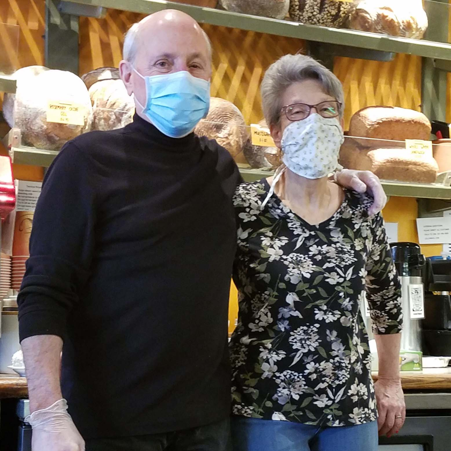 man and woman wearing masks in bakery