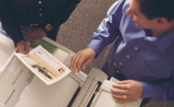 Two individuals making copies inside the UPS Store.