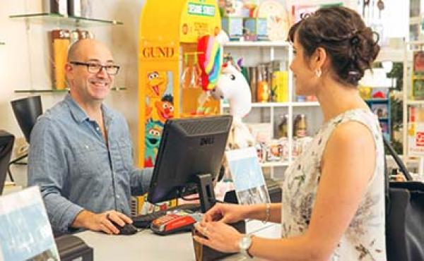 smiling man talking to woman in shop
