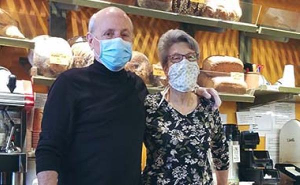 bald man and wife wearing masks in bakery