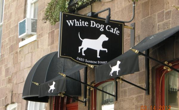 Hanging sign with logo outside of White Dog Cafe