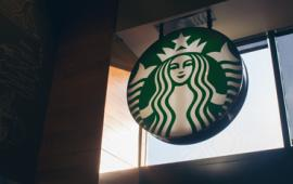 Starbucks logo sign inside a Starbucks cafe.