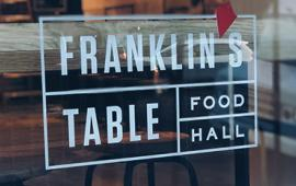 Photo of Franklin's Table logo on food hall window